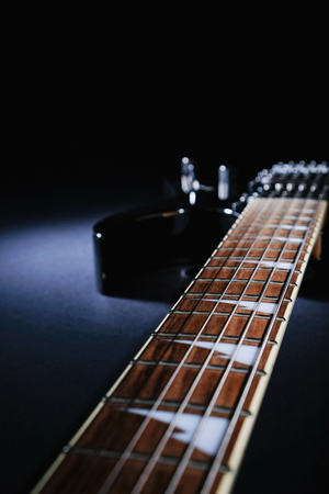 Electric guitar   on a dark background under beam of light. with copy space Stock Photo
