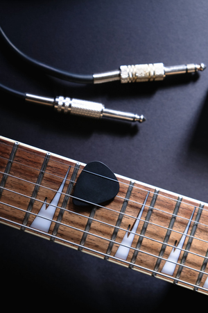 Guitar frets with strings and mediator, jack cable on dark background Stock Photo