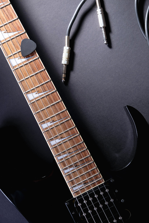 Modern black electric guitar with jack cable on black background Stock Photo