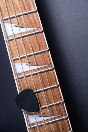 Guitar frets with strings and mediator on dark background