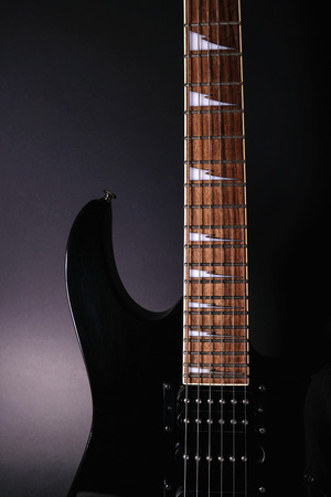 Body and neck of electric guitar. Close up detail. Accentuated shapes by illumination. With copy space on dark backgrouna