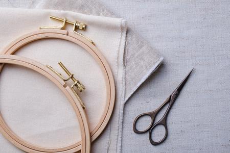 Insieme del ricamo. Tessuto di lino bianco, telaio da ricamo, fili e aghi colorati. Copia spazio Archivio Fotografico