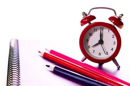 School time minimalistic concept. Colored pencils and notebooks and a red alarm clock.Time management. Zdjęcie Seryjne
