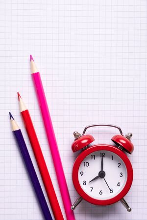School time minimalistic concept. Colored pencils and notebooks and a red alarm clock. Top view  Zdjęcie Seryjne