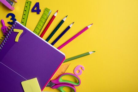 Office and student gear over lilac and yellow background - Back to school concept. Top view