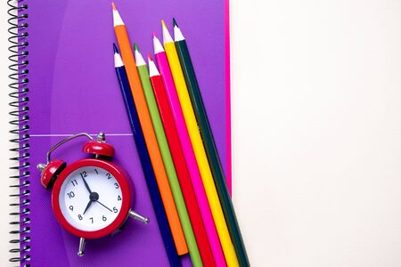 Colored pencils and purple notebooks and a red alarm clock. School and office supplies. Top view.