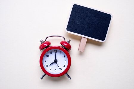 Blank vintage small chalkboard for text on purple background and a red alarm clock. . Minimal concept