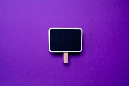 Blank vintage small chalkboard for text on purple background . Minimal concept Zdjęcie Seryjne