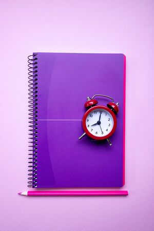 Red alarm clock on lilac blank note for text. Reminder. Space for copy. Minimal concept.