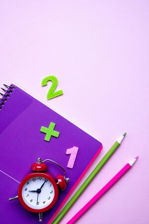 Colorful pencils lying on a purple notebook and red alarm clock. Back to school concept. Time management. Top view Zdjęcie Seryjne