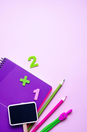 Colored different school supplies on lilac paper background. Back to school concept. Flat lay, top view, copy space