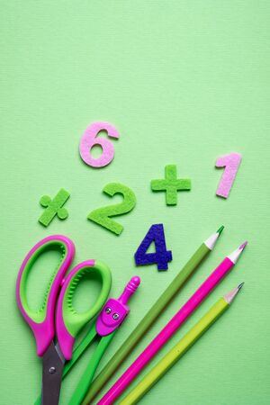 Colored different school supplies on light green paper background. Back to school concept. Flat lay, top view, copy space