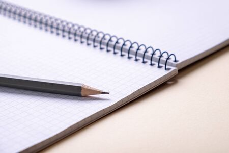 top view of a open  school notebook  with a spiral spring, office notepad in diagonal with  pencil
