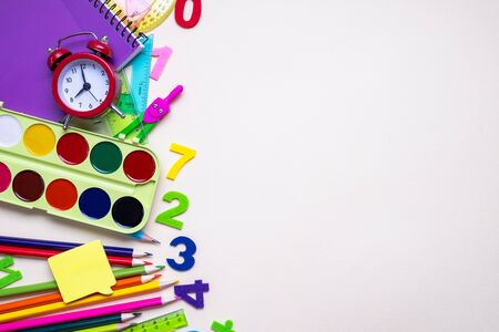 Colored different school supplies on light paper background. Back to school concept. Flat lay, top view, copy space