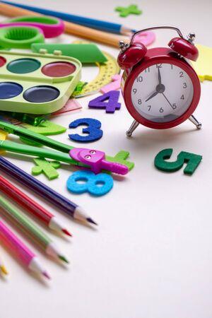 Concept back to school. Alarm clock and School supplies.