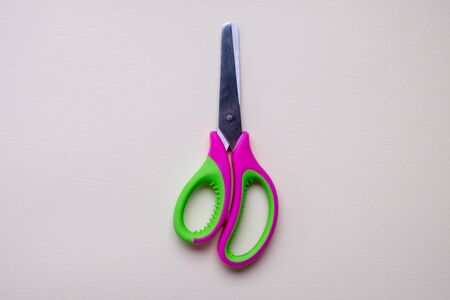 Top view of a pair ofgreen and pink plastic  scissors isolated on light background Zdjęcie Seryjne