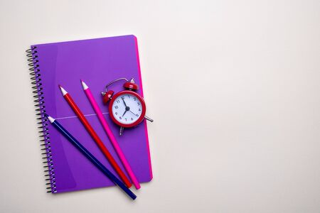 Time management concept. Red vintage alarm clock, pencils and purple  notepad