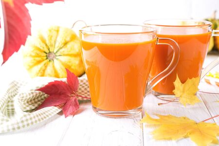 Seasonal autumn thanksgiving concept. Pumpkin fresh juice drink cocktail on a white table with fall maple leaves. Copy space