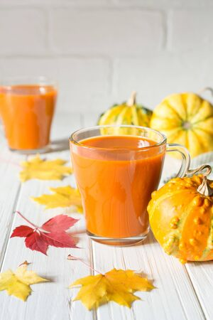 Fresh pumpkin juice or smoothie. Fall drink concept. On white background