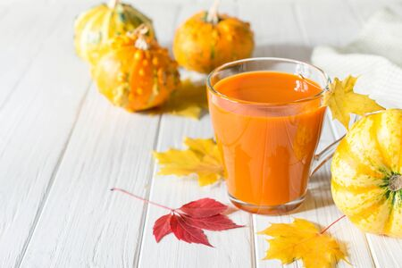 Traditional autumn drink. Glass cups of pumpkin juice, pumpkins and fallen maple leaves
