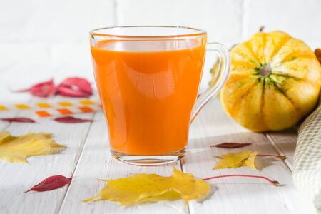 Glass of fresh pumpkin smoothie on white wooden background