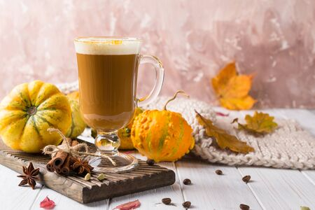 Cup of pumpkin spice latte with whipped cream on top and seasonal autumn spices, and fall decor. Traditional coffee drink for autumn or winter holidays, copy space.