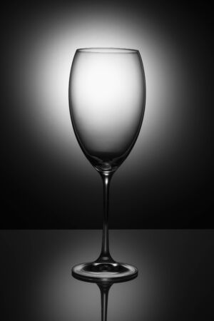Transparent  glass goblet without wine on a thin leg stands on a mirror surface. Stockfoto