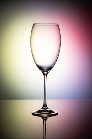 Empty wine glass goblets on a colored background abstract