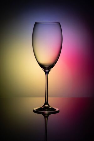 Empty glass goblet without wine on a thin leg stands on a mirror surface. Colorful background.