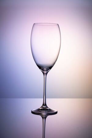 Empty glass goblet without wine on a thin leg stands on a mirror surface. Colorful purple background.