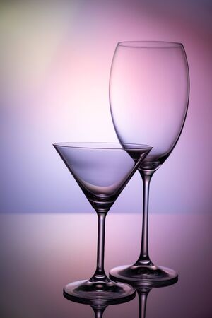 Empty glass goblets set. On a colored purple background abstract Stockfoto - 129800327