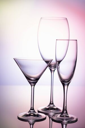 Empty glass goblets set. On a colored purple background abstract Stockfoto