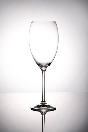 Empty wine glass goblets stands on a mirror surface on white background Stockfoto - 129800331