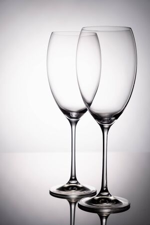 Two glass goblet without wine on a thin leg stands on a mirror surface.
