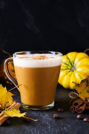 Pumpkin spiced latte or coffee in glass cup, dry leaves. Traditional autumn or winter hot drink. Stockfoto
