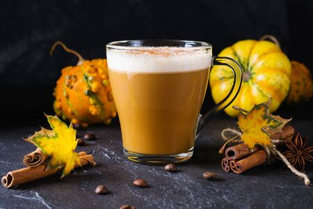 Traditional autumn dishes. Halloween, Thanksgiving. Mug of  hot and spicy aromatic pumpkin latte with whipped cream on top. Ingredients for cook spicy pumpkin latte on dark  background