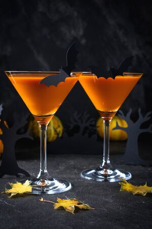 Orange martini cocktails with bats and decor for Halloween party, on dark background