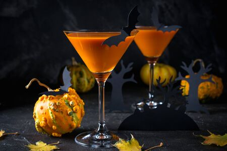 Orange pumpkin, Halloween drink for party and holiday decorations over black background with copy space