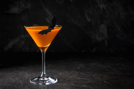 Orange pumpkin  martini Halloween drink for party over black background with copy space