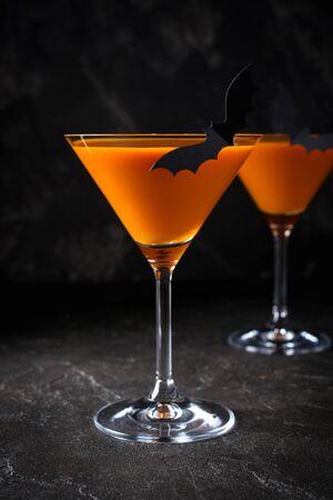 Orange citrouille martini Halloween boisson pour la fête sur fond noir avec copie espace Banque d'images