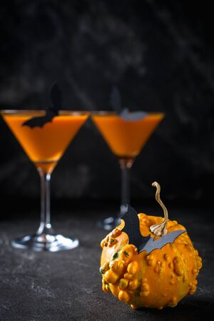 Funny Pumpkin with black bats and orange cocktail in a glass on Halloween