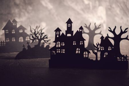 Halloween night background. Paper art. Abandoned village in a dark misty forest