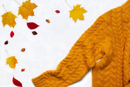 Autumn composition.Warm yellow knitted sweater, leaves on white background. Flat lay, top view, copy space