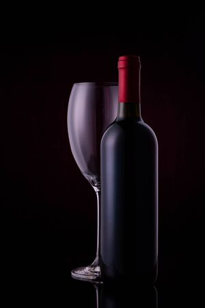 Red wine glass and a wine bottle with reflections on black background