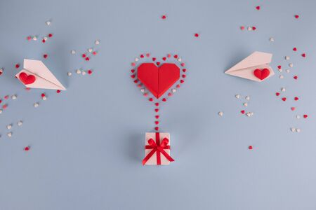Love concept - Valentines day, anniversary or wedding celebration concept. Flat lay. Top view. Copy space. Origami paper heart balloon with gift box flying. On pastel blue background. Stock fotó