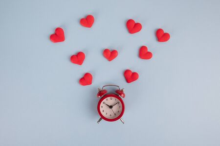 Valentines Day background. Red alarm clock and red hearts around it on a blue background. Time for love.
