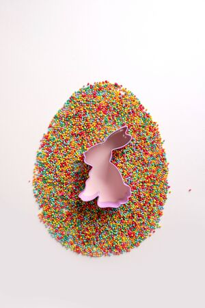 Bunny shape cookie cutters with multicolored confectionery topping isolated on a white Archivio Fotografico