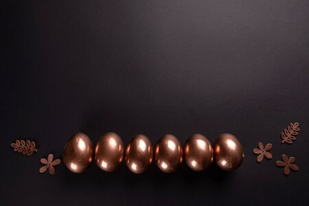 Row of gold Easter eggs on black background. Flat lay, Top view, copy space. Miniml easter concept
