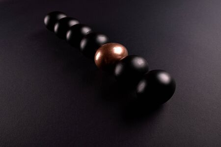One golden egg and black eggs lie in a row on black background with copy space Stock Photo