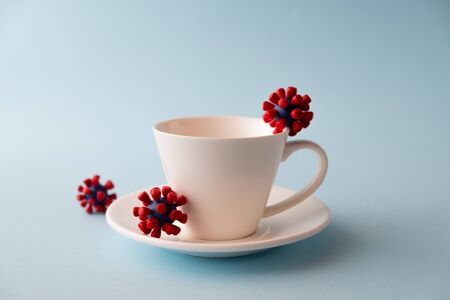 White cup with models of covid-19 virus on blue background. Epidemic coronavirus. Risk of infection COVID-19 concept. Place fo text Foto de archivo